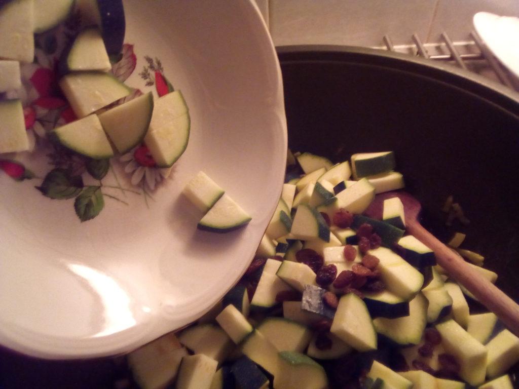 Après avoir fait revenir l'ail, l'oignon et les épices, ajouter les courgettes et les raisons secs.
