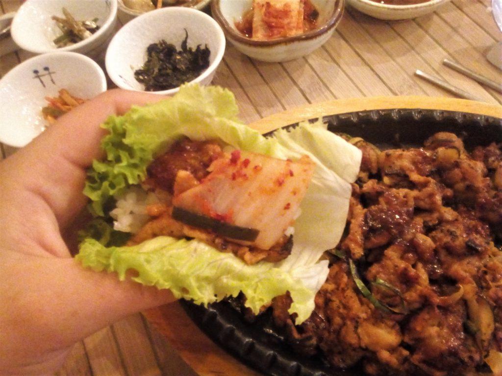 """Dégustation """"façon barbecue coréen"""", où l'on enroule le riz, la viande et les accompagnements dans une feuille de salade."""