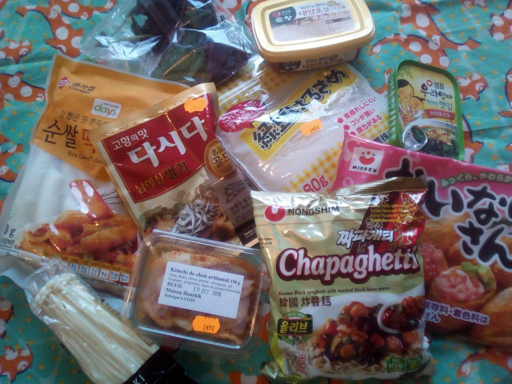 De gauche à droite et de haut en bas : feuilles de shiso, gochujang (pâte de piment fermentée), tteok (cylindres de pâte de riz gluant), bouillon d'anchois en poudre, vermicelles d'amidon de pomme de terre, feuilles de sésame marinées, champignons enoki, kimchi artisanal (chou fermenté au piment), nouilles instantanées à la sauce noire et inari (peau de tofu frit marinée).