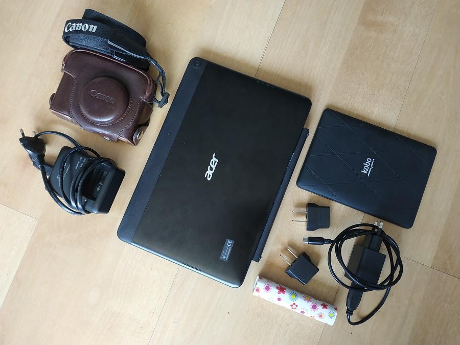 Mon matériel électronique de voyage : tablette avec clavier, liseuse, appareil photo Canon G12, batterie externe, chargeurs et adaptateurs.