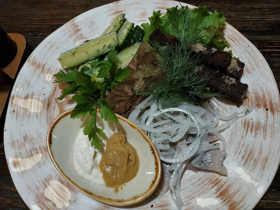Après avoir bien déambulé, nous nous sommes offert un festin de plats typiquement sibériens. Crème de champignons, raviolis sibériens (pelmeny), croquettes de brochet, légumes rôtis, steak à la confiture d'airelles... Il y en avait plein la table ! Le tout arrosé de thé à l'argousier, au gingembre et au romarin. Ici vous voyez un assortiment de hors-d'œuvres : concombres marinés au sel et à l'ail (hhmmmm), pâté à la gelée (il n'y a que moi qui en ai mangé xD), croûtons de pain à l'ail (TRÈS bons), hareng à l'huile, pickles d'oignon, moutarde EXTRA-forte et crème de raifort.