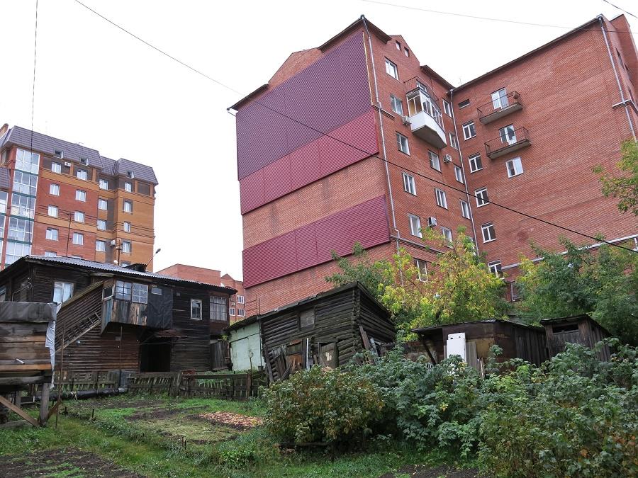 Certaines maisons en bois se mêlaient aux immeubles modernes d'une manière plutôt incongrue.