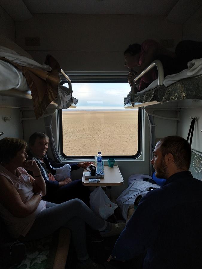 A bord du Transmongolien, sur la portion entre Oulan-Bator et Pékin. Il n'y a pas de 3ème classe, j'ai donc dû réserver un lit dans un compartiment quatre couchettes. Mon pote Antoine, rencontré en Mongolie, taille la bavette avec le couple de Français très sympa qui partageait mon compartiment. Derrière eux défile le désert de Gobi...