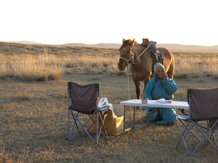 """Nous étions arrivés depuis à peine dix minutes qu'une """"voisine"""" (dont la yourte se trouvait à 1 km) nous a payé une petite visite avec son cheval. Tout naturellement, sans question ni commentaire, Tsogo lui a aussitôt servi du thé. Puis elle nous a placidement regardés préparer le repas et monter les tentes. Enfin, elle a mangé la soupe bien chaude avec nous et, dès que le soleil s'est couché, elle a sauté à dos de cheval. Alors qu'elle s'éloignait dans le couchant, sa silhouette noire se découpait sur le ciel en feu. On s'est tous jetés sur nos appareils photo, mais c'était trop tard : l'instant le plus photogénique de notre séjour ne pourrait rester imprimé que sur nos rétines ;)"""