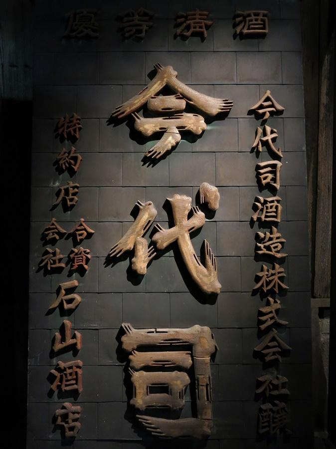 Cette enseigne de la brasserie de saké Imayo Tsukasa se trouvait sur le toit de l'ancienne fabrique. Les kanji (caractères sino-japonais) sont taillés dans du bois de cèdre, le même qu'on utilisait pour la fabrication des fûts de fermentation.