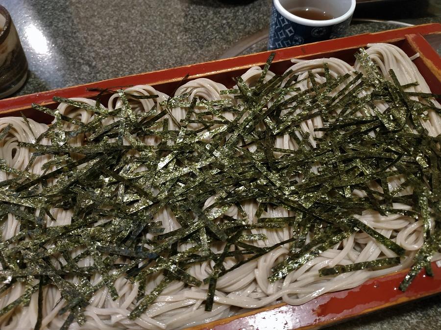 Au centre, la star du repas : une grande portion de nouilles hegisoba, qui sont une variante des éternelles nouilles de sarrasin japonaises, appelées soba. Dans la pâte de ces soba à la mode de Niigata, on a ajouté de l'algue funori, qui leur donne une texture plus souple et plus de mâche. Elles sont généralement servies froides, sur un plateau de bois ajouré, et séparées en petites portions de la taille d'une bouchée. Ici, elles sont également recouvertes de franges d'algue nori (la même qu'on utilise dans les sushis !).