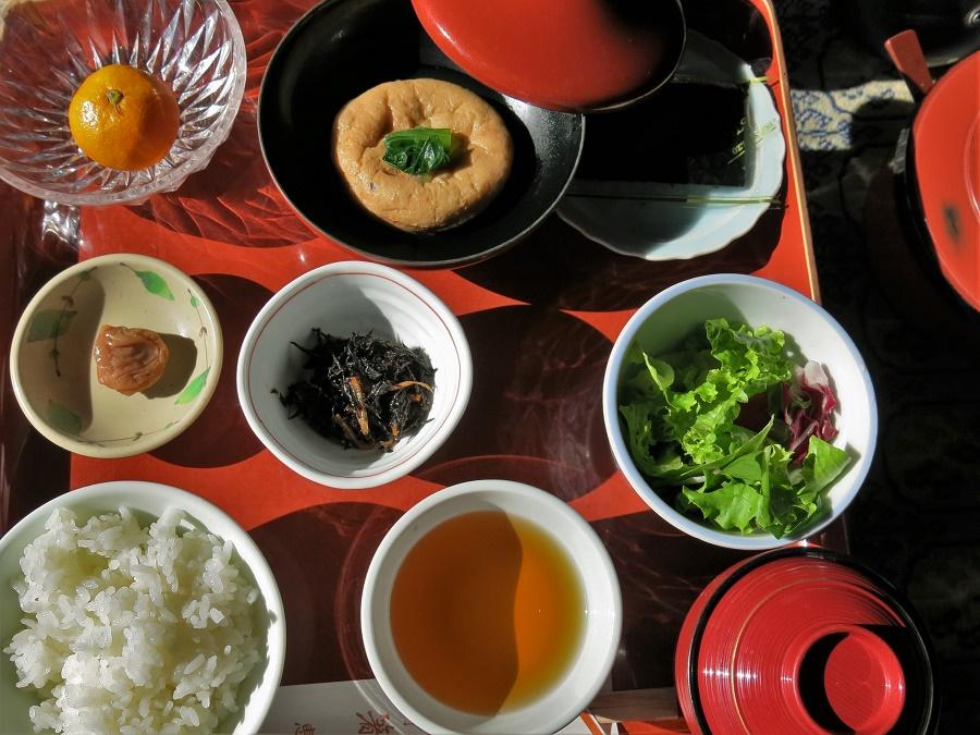 Au menu de ce petit-déjeuner, évidemment végétarien (et même végane !) : mikan (clémentine japonaise), tofu imbibé de bouillon sucré-salé, algues nori séchées (les mêmes que sur les sushis, dont on peut se servir pour envelopper le riz), umeboshi (prune salée au goût acidulé, qu'on utilise comme condiment pour accompagner le riz), algues hijiki mijotées, petite salade verte, riz, thé torréfié et soupe miso. Au top !!