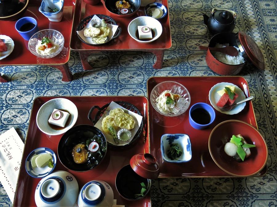 Plateau de gauche : gomadofu à la sauce soja, tempura (beignets) de légumes, tofu mariné et algues wakame servis dans une gelée aigre-douce au vinaigre de riz (un délice !), pickles de daïkon et de sansai, bouillon de champignons shiitake au negi. Plateau de droite : nouilles glacées à tremper dans un bouillon dashi végétarien, légumes verts mijotés, tofu frit à la pomme de terre gluante et fruits en dessert.