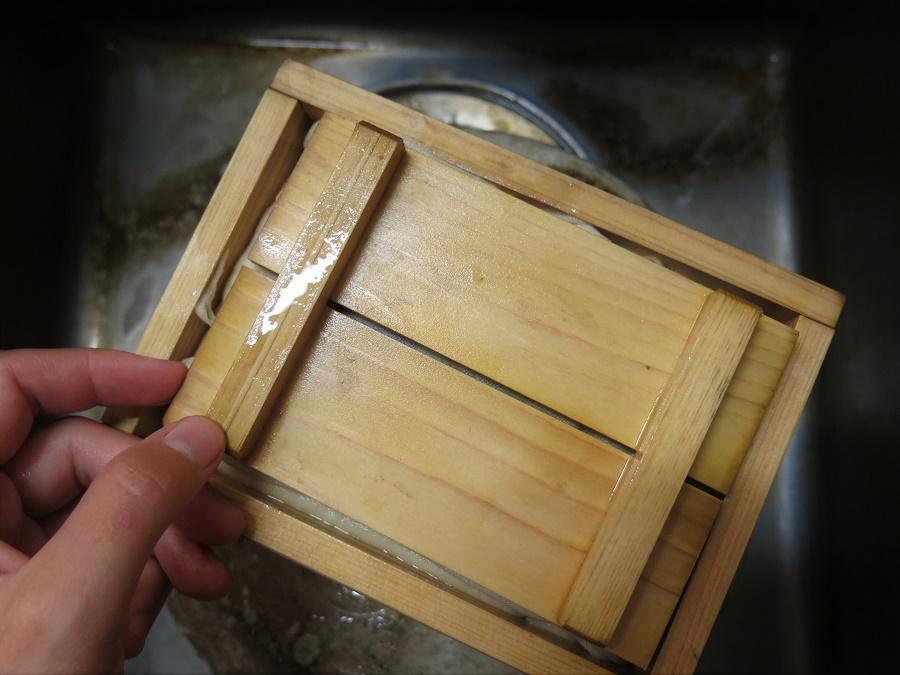 Placez un couvercle bien plat sur votre tofu maison, et surtout légèrement plus petit que le moule : cela vous permet d'y déposer un poids, afin de presser le tofu et de lui faire rendre son eau pendant 15 à 30 min.