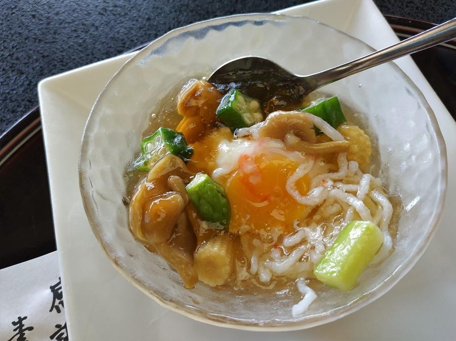 """""""Onsen"""", comme vous le savez, signifie """"source chaude"""" - et """"tamago"""" signifie """"œuf"""". Or, au Japon il existe une tradition qui consiste à faire cuire des œufs à basse température dans l'eau des onsen (souvent autour de 65-75°C), ce qui leur donne une excellente texture fondante. C'est un œuf de ce type, à mi-chemin entre mollet et à la coque, que l'on m'a servi en entrée froide, dans un consommé en gelée très léger. Il y avait également des nouilles fondantes et de petits légumes croquants : asperges, champignons nameko, maïs et gombos."""