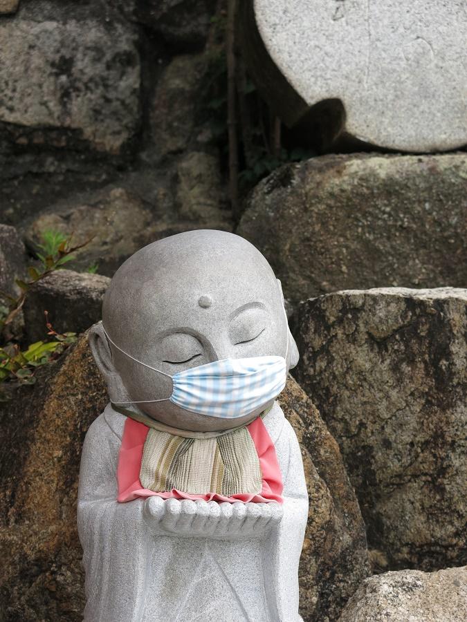 Une statue de la divinité Jizô, protecteur des voyageurs et des bébés dans la foi japonaise shintô, bien protégé par son petit masque en tissu sur-mesure.