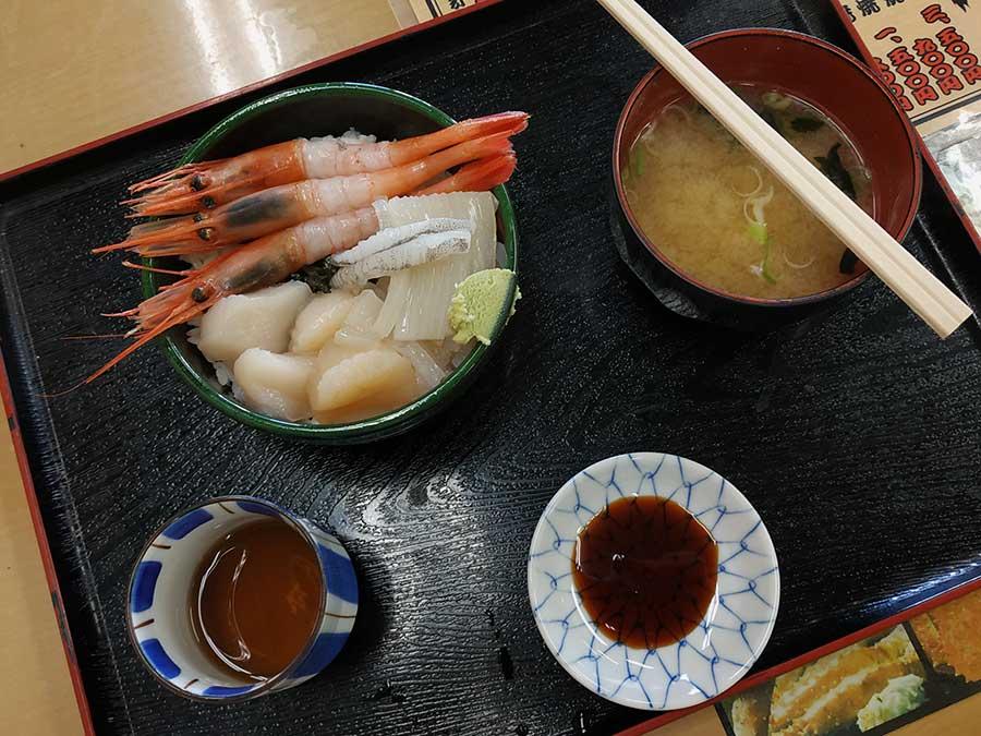 """La raison pour laquelle les touristes adorent le marché Asaichi, c'est que de nombreux étals et restaurants spécialisés y proposent des """"donburi"""". Il s'agit de bols de riz tiède, sur lesquels les gourmands font disposer leurs poissons et fruits de mer préférés. Tous sont crus et, pour peu qu'on ait bien choisi sa boutique, d'une fraîcheur imbattable... Pour ma part, j'ai choisi des crevettes crues, dont je raffole, et deux incontournables de la région : seiche fondante et noix de Saint-Jacques. Le tout servi avec un peu d'algues nori, une bonne dose de moutarde wasabi, de la sauce soja, une soupe miso et du thé grillé. Ah là là, rien que de vous l'écrire, j'en salive à nouveau... ;)"""