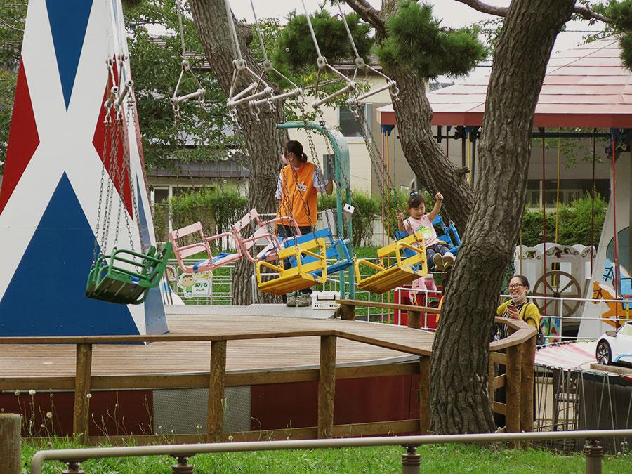"""Sur mon chemin, j'ai d'abord traversé le joli (et bien nommé) """"parc d'Hakodate"""" où, en ce tiède dimanche, les parents avaient amené leurs enfants courir entre les pins ou faire un tour de manège. Dans le micro-parc d'attractions et le petit zoo gratuit, tout était minuscule et rétro : je me serais crue dans une foire de village des années cinquante ! De la musique grésillante aux chevaux de bois, tout y était. Seules les auto-tamponneuses en forme de pokemon détonnaient ;)"""