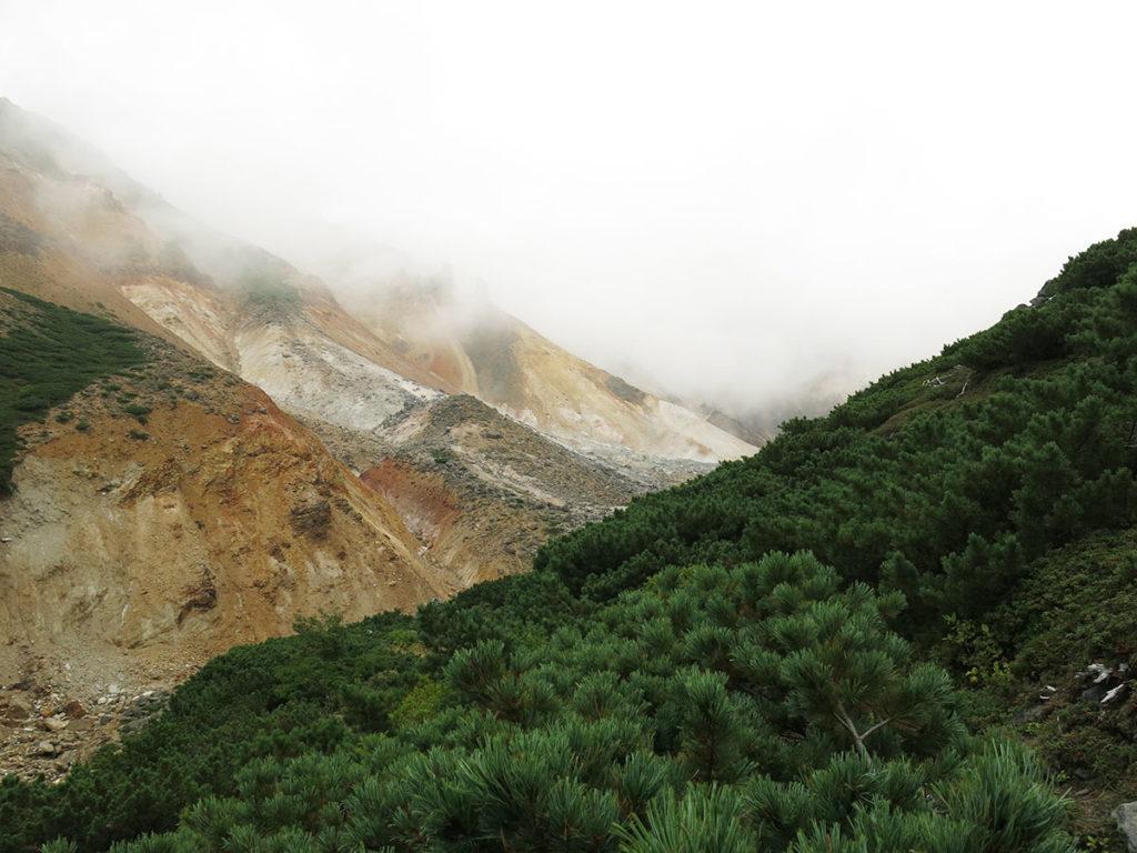 """Au départ de l'arrêt """"Tokachidake-Onsen"""", la plupart des randonneurs se lancent à l'attaque du mont Tokachi, qui culmine à 2077 mètres d'altitude. Une fois de plus, j'ai dû renoncer à ce projet à cause de la météo incertaine, et surtout parce que j'avais une autre idée encore plus excitante..."""
